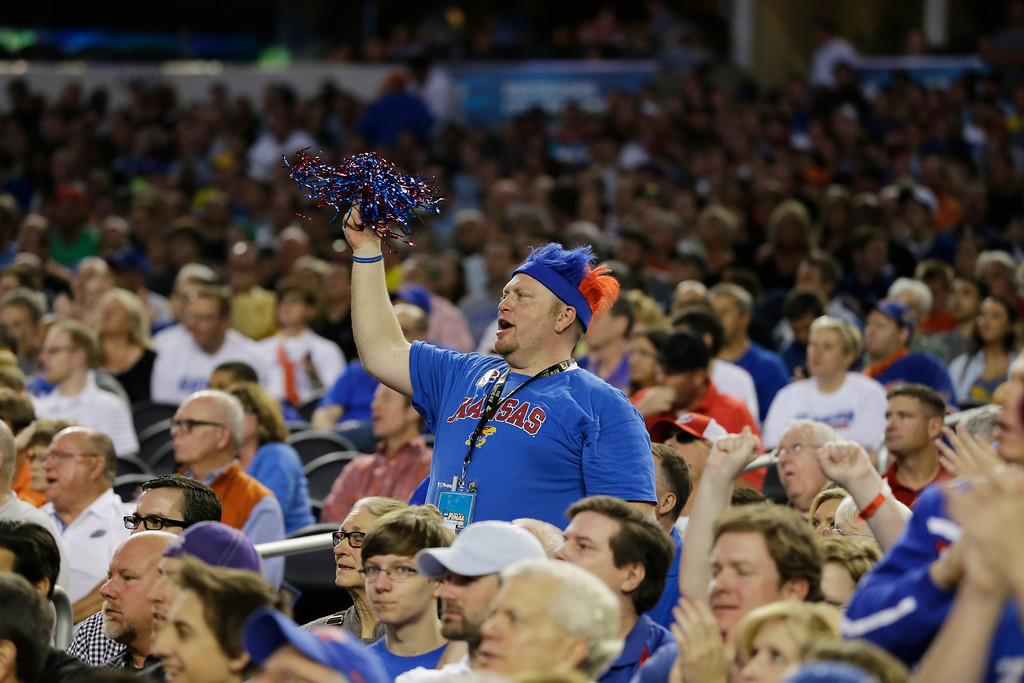 Description of . A Kansas fan cheers the team during the first half of a regional semifinal game against Michigan in the NCAA college basketball tournament, Friday, March 29, 2013, in Arlington, Texas. (AP Photo/Tony Gutierrez)