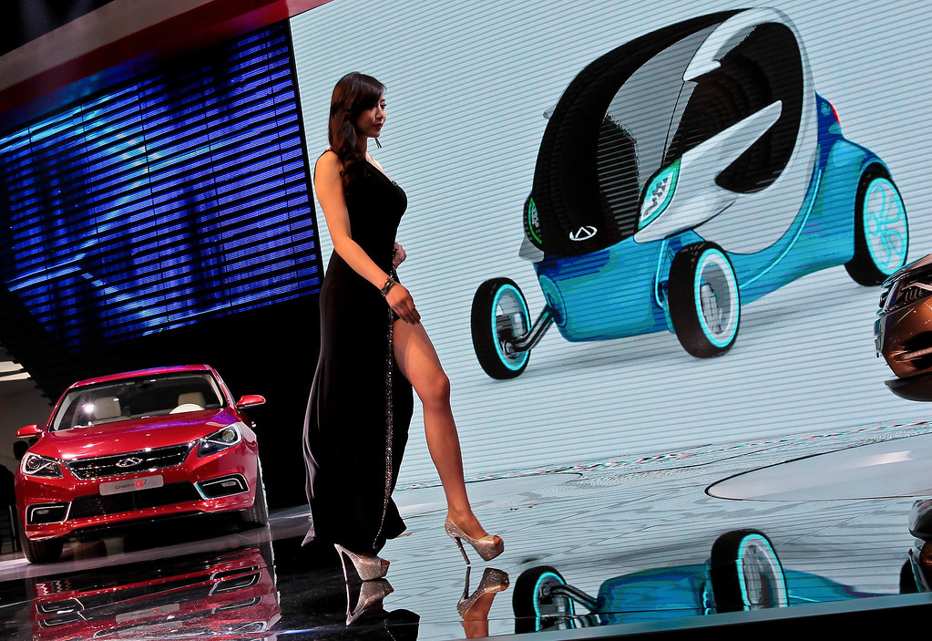 Description of . A model walks past Alpha 7 car, left, and @ANT2.0 concept car shown on the screen, made by Chinese automaker Chery on display at the Shanghai International Automobile Industry Exhibition (AUTO Shanghai) media day in Shanghai Saturday, April 20, 2013. (AP Photo)