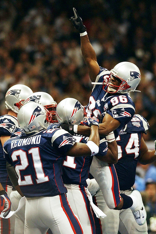 . New England Patriots\' receiver David Patten (R-Jumping) celebrates his touchdown with teammates after catching a pass from Tom Brady during first half action 03 February, 2002, of Super Bowl XXXVI in New Orleans, Louisiana. STAN HONDA/AFP/Getty Images