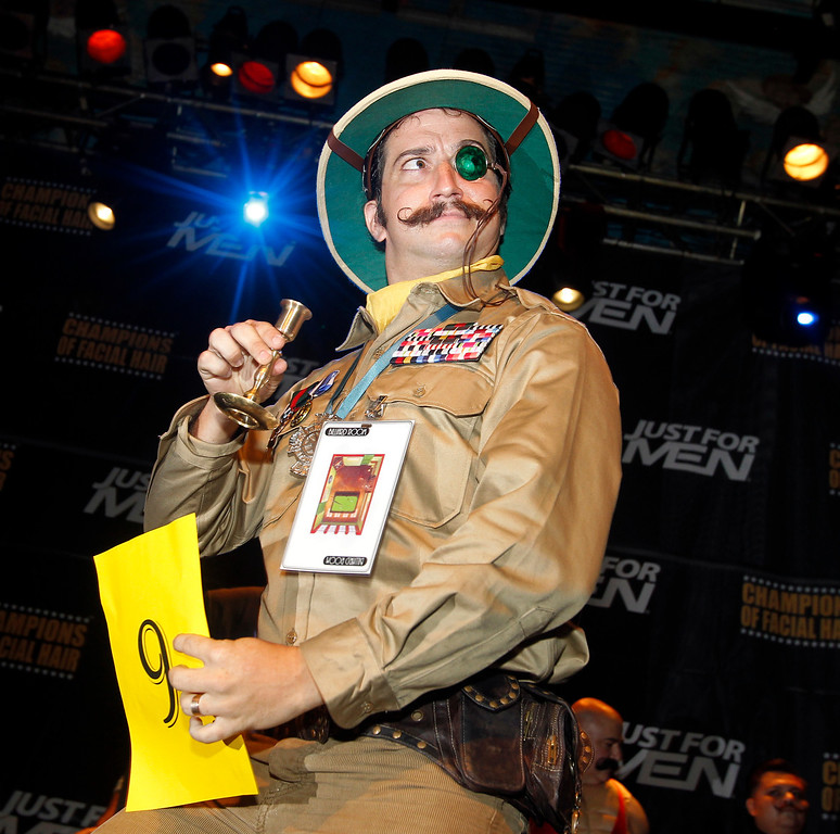 Description of . Adam Scott strikes a pose as he competes in the Imperial Mustache division during the fourth annual Just For Men National Beard and Moustache Championships Saturday, Sept. 7, 2013 at The House of Blues in New Orleans. More than 150 contestants competed in 18 different categories including Dali, full beard natural and sideburns. (AP Photo/Susan Poag)