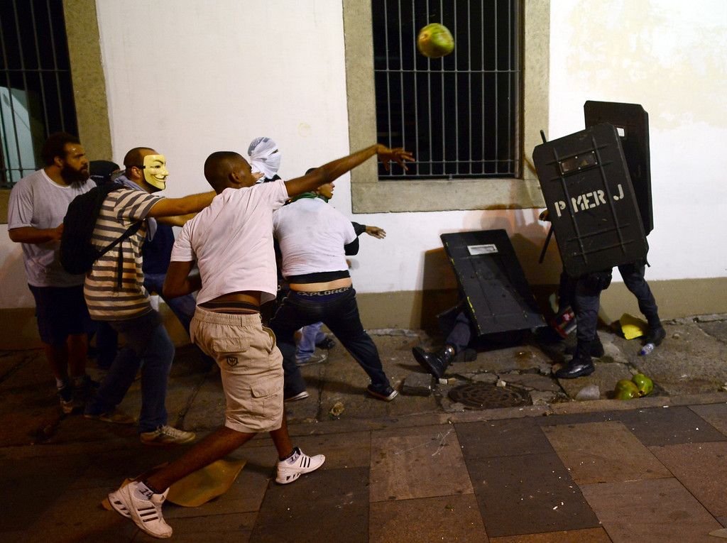 Description of . A demonstrator throws a coconut at anti riot policemen during clashes in downtown Rio de Janeiro on June 17, 2013, after a protest against higher public transportation fares and the use of public funds to finance international football tournaments. Protesters in several major cities are up in arms over hikes in mass transit prices -- from $1.5 to $1.6 -- as well as over the $15 billion earmarked for the two sports events amid calls for more health and education funding. CHRISTOPHE SIMON/AFP/Getty Images