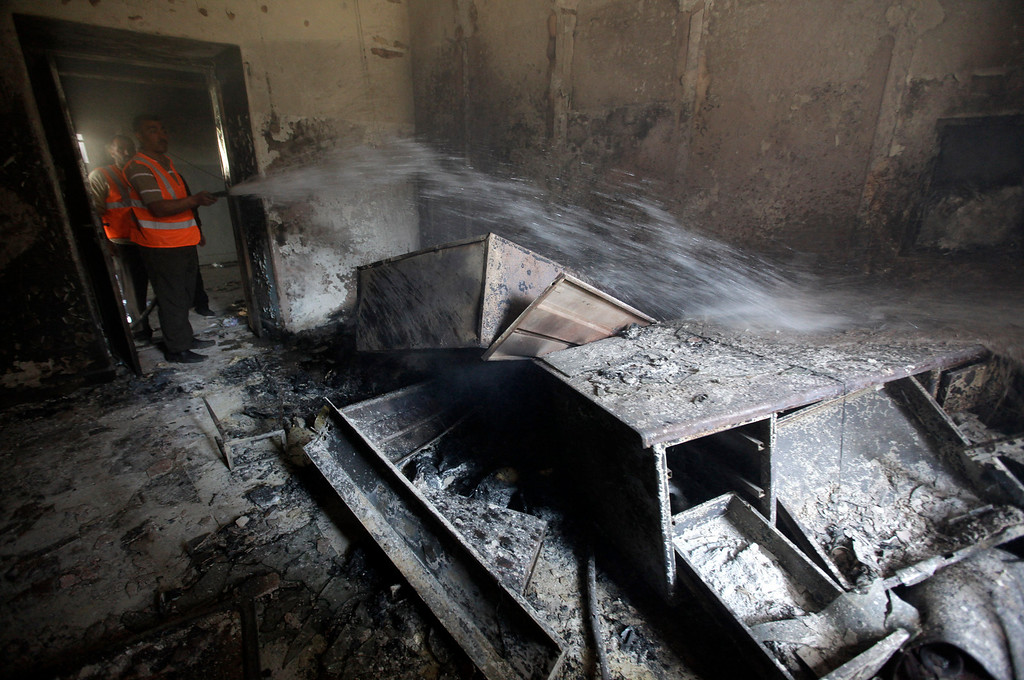 Description of . FILE - A Syrian municipality worker extinguishes a burned court room that was set on fire by Syrian anti-government protesters, in the southern city of Daraa, Syria, Monday, March 21, 2011. (AP Photo/Hussein Malla, File)