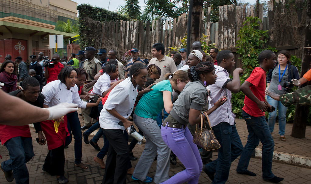 Description of . Civilians who had been hiding inside during the gun battle manage to flee from the Westgate Mall in Nairobi, Kenya Saturday, Sept. 21, 2013.  (AP Photo/Jonathan Kalan)