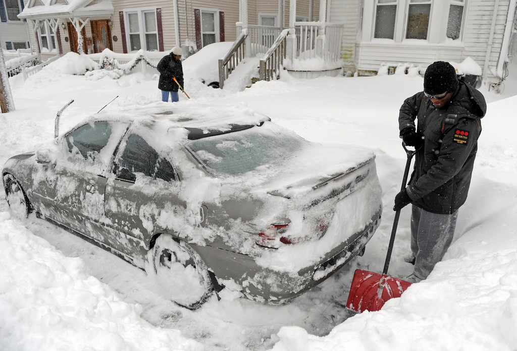 . Aaron Powell digs out his car as Brenda Thomas, back, clears her walk along McKinley Avenue, Saturday, Feb. 9, 2013, after a snow storm in Norwich, Conn. (AP Photo/The Day, Sean D. Elliot)
