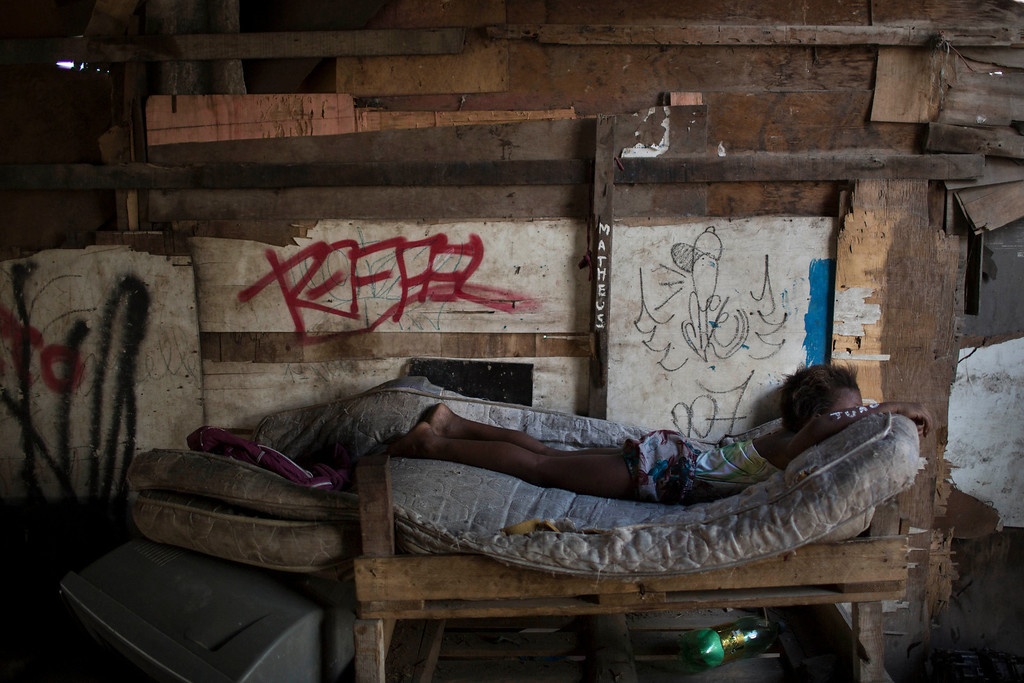 Description of . A girl lays on a mattress placed under a bridge in a poor area of the Mare slum complex in Rio de Janeiro, Brazil, Saturday, April 5, 2014. More than 2,000 Brazilian soldiers stormed into the slum complex Saturday with armored personnel carriers and helicopters in a bid to improve security two months before the start of the World Cup. (AP Photo/Felipe Dana)