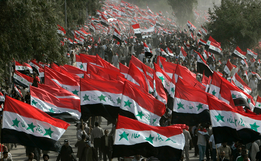 Description of . Demonstrators wave Iraqi flags during an anti-U.S. protest called by fiery cleric Moqtada al-Sadr in Najaf, marking the fourth anniversary of the fall of Baghdad April 9, 2007. Baghdad was under curfew on the fourth anniversary of the fall of the capital to U.S. forces.  REUTERS/Ceerwan Aziz