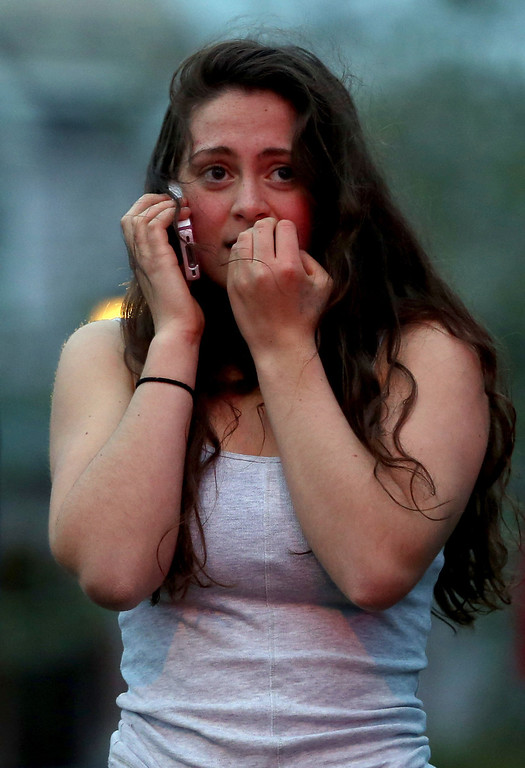 Description of . WATERTOWN, MA - APRIL 19: Resident Rosie Meyer, who said she heard gunshots, reacts while watching police respond on April 19, 2013 in Watertown, Massachusetts. After a car chase and shoot out with police, one suspect in the Boston Marathon bombing, Tamerlan Tsarnaev, 26, was shot and killed by police early morning April 19, and a manhunt is underway for his brother and second suspect, 19-year-old suspect Dzhokhar A. Tsarnaev. The two men, reportedly Chechen of origin, are suspects in the bombings at the Boston Marathon on April 15, that killed three people and wounded at least 170.  (Photo by Mario Tama/Getty Images)