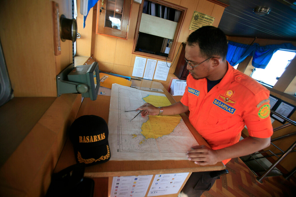 Description of . An Indonesian Search And Rescue (SAR) member looks at a map during a search operation for the missing Malaysian Airlines airplane in the Malacca straits, near Aceh Sea, Sumatera, Indonesia, 12 March 2014.  EPA/HOTLI SIMANJUNTAK