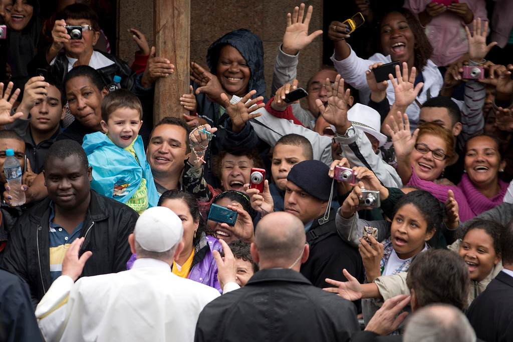 Description of . People greet and take pictures of Pope Francis as he visits the Varginha slum in Rio de Janeiro, Brazil, Thursday, July 25, 2013. Francis on Thursday visited one of Rio de Janeiro's shantytowns, or favelas, a place that saw such rough violence in the past that it's known by locals as the Gaza Strip. (AP Photo/Victor R. Caivano)