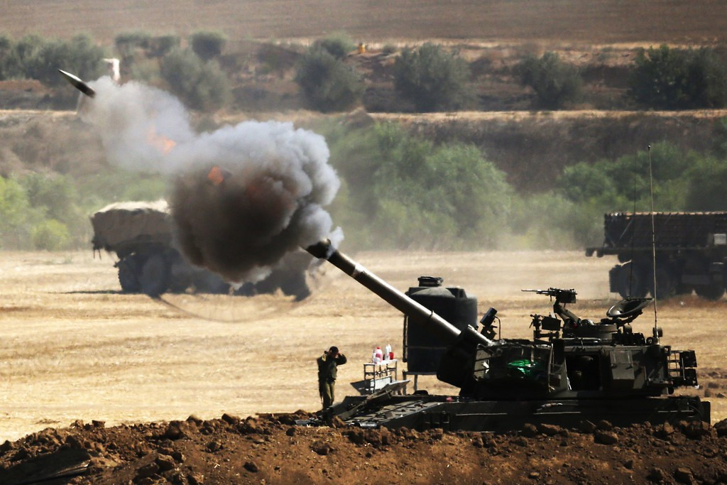 Description of . An Israeli artillery gun fires a 155mm shell towards targets from their position near Israel's border with the Gaza Strip on July 30, 2014. Israel agreed to observe a four-hour lull in Gaza several hours after a deadly strike on a school killed 16, drawing a furious response from a UN refugee agency. AFP PHOTO/ JACK  GUEZ/AFP/Getty Images