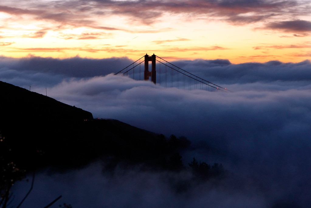 Description of . The north tower of the Golden Gate Bridge is blanketed by fog as the sun rises October 8, 2007 in Sausalito, California. (Photo by Justin Sullivan/Getty Images)