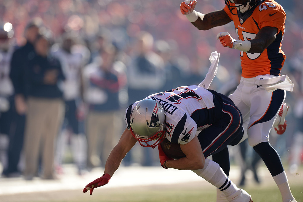 Description of . Denver Broncos cornerback Dominique Rodgers-Cromartie (45) hits New England Patriots wide receiver Julian Edelman (11) after he makes a catch in the first quarter. The Denver Broncos take on the New England Patriots in the AFC Championship game at Sports Authority Field at Mile High in Denver on January 19, 2014. (Photo by Hyoung Chang/The Denver Post)