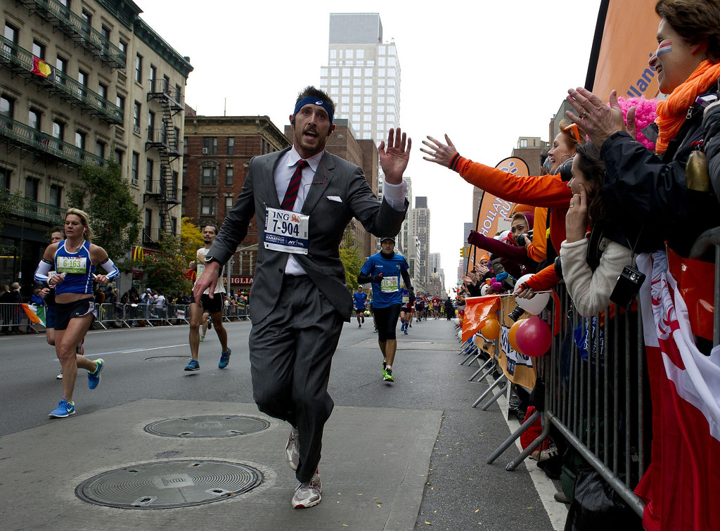 Description of . A man in a suit runs up First Avenue November 3, 2013 during the running of the New York City Marathon in New York.    DON EMMERT/AFP/Getty Images
