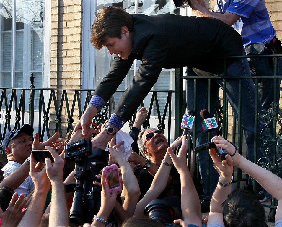 Description of . In this March 14, 2012 file photo, former Illinois Gov. Rod Blagojevich reaches over a railing to shake supporters' hands at his home in Chicago. The 55-year-old Democrat was due to report to a prison in Colorado to begin serving a 14-year sentence, making him the second Illinois governor in a row to go to prison for corruption. (AP Photo/Charles Rex Arbogast, File)