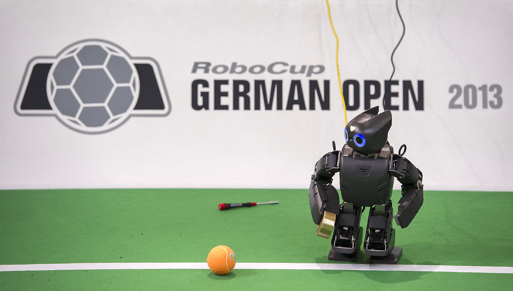 Description of . MAGDEBURG, GERMANY - APRIL 26:  A robot in the play field at the 2013 RoboCup German Open tournament on April 26, 2013 in Magdeburg, Germany. The robots, which are a model called Nao, manufactured by Aldebaran Robotics, perform autonomously and communicate with one another via WLAN. The three-day tournament is hosting 43 international teams and 158 German junior teams that compete in a variety of disciplines, including soccer, rescue and dance.  (Photo by Jens Schlueter/Getty Images)