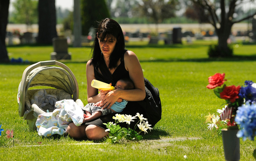 Description of . Krista Adams, with her new five-week-old baby son, Michael Adams, visits the grave of her son, Julian Adams Lacas, Friday, June 06, 2012, at Elmwood Cemetery in Brighton. Her son was killed  by his father who is currently serving a 48 year prison sentence. This was the first time she has brought her new son to grave site. Krista Adams brought her sister Melissa Adams with her for support. RJ Sangosti, The Denver Post