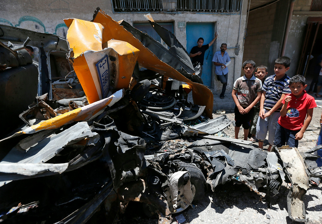 Description of . Palestinians gather around a vehicle that was destroyed by a Israeli missile strike in Khan Younis, southern Gaza Strip on Wednesday, July 16, 2014. Hundreds of Palestinian families, their children crying, fled Wednesday, as Israel intensified airstrikes on Hamas targets, including homes of the movement's leaders, following failed Egyptian cease-fire efforts. Before the renewed bombardment, Israel had told tens of thousands of residents of border areas to evacuate their neighborhoods. (AP Photo/Lefteris Pitarakis)