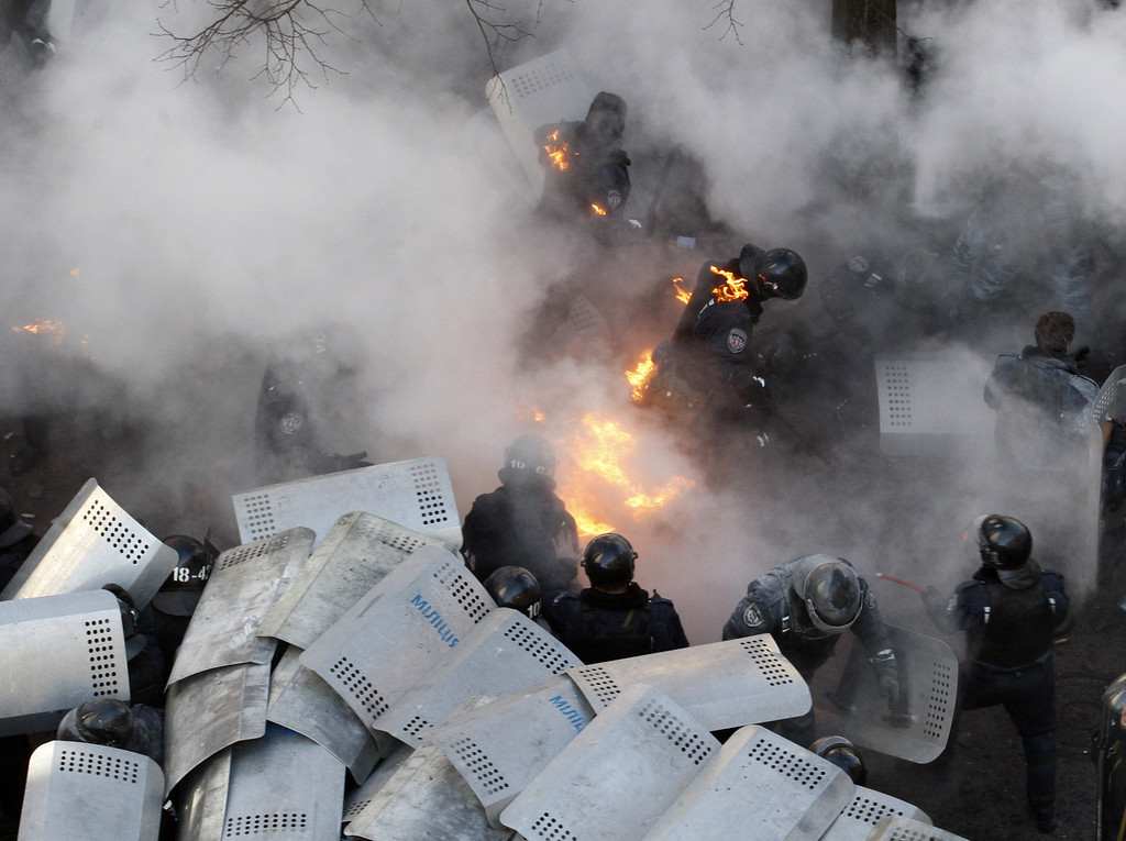 Description of . Policemen run amid flames during clashes with anti-government protesters in front of the Ukrainian Parliament in Kiev on February 18, 2014. AFP PHOTO/ ANATOLII STEPANOV/AFP/Getty Images