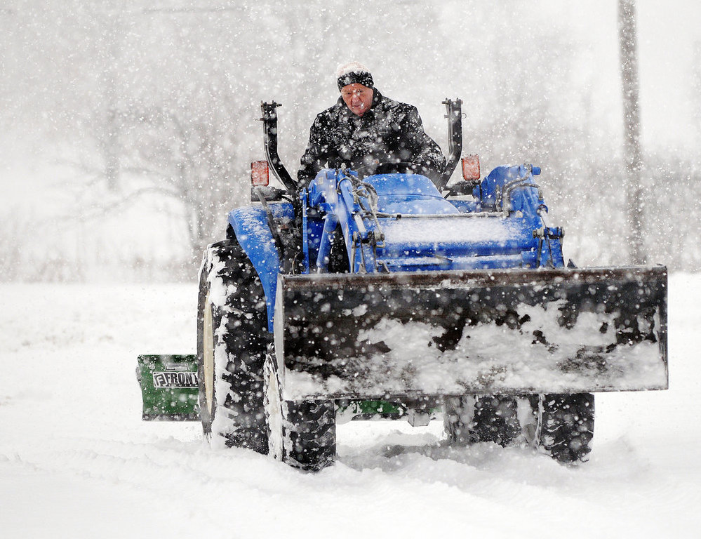 Description of . Kent Farley clears a parking lot of snow on Tuesday, March 5, 2013, in Coal Valley, Ill. (AP Photo/The Dispatch, Todd Mizener)