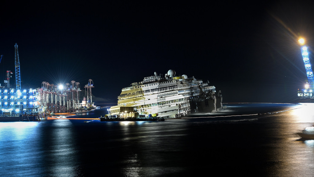 Description of . The wreck of Italy's Costa Concordia cruise ship begins to tip to an upright postion on September 17, 2013 near the harbour of Giglio Porto, as salvage crews worked to raise the ship in the largest and most expensive maritime salvage operation in history. The crews used a method called