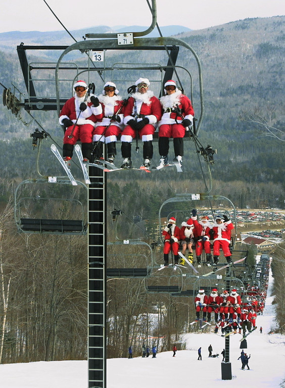 Description of . Skiers and snowboarders dressed as Santa Claus ride up the ski lift, Sunday, Dec. 8, 2002 at Sunday River in Newry, Maine.  About 250 skiers turned up dressed as Santa to ski for free and raise money for the Bethel (Maine) Rotary Club's Annual Dinner for Families in Need. (AP Photo/Joel Page)
