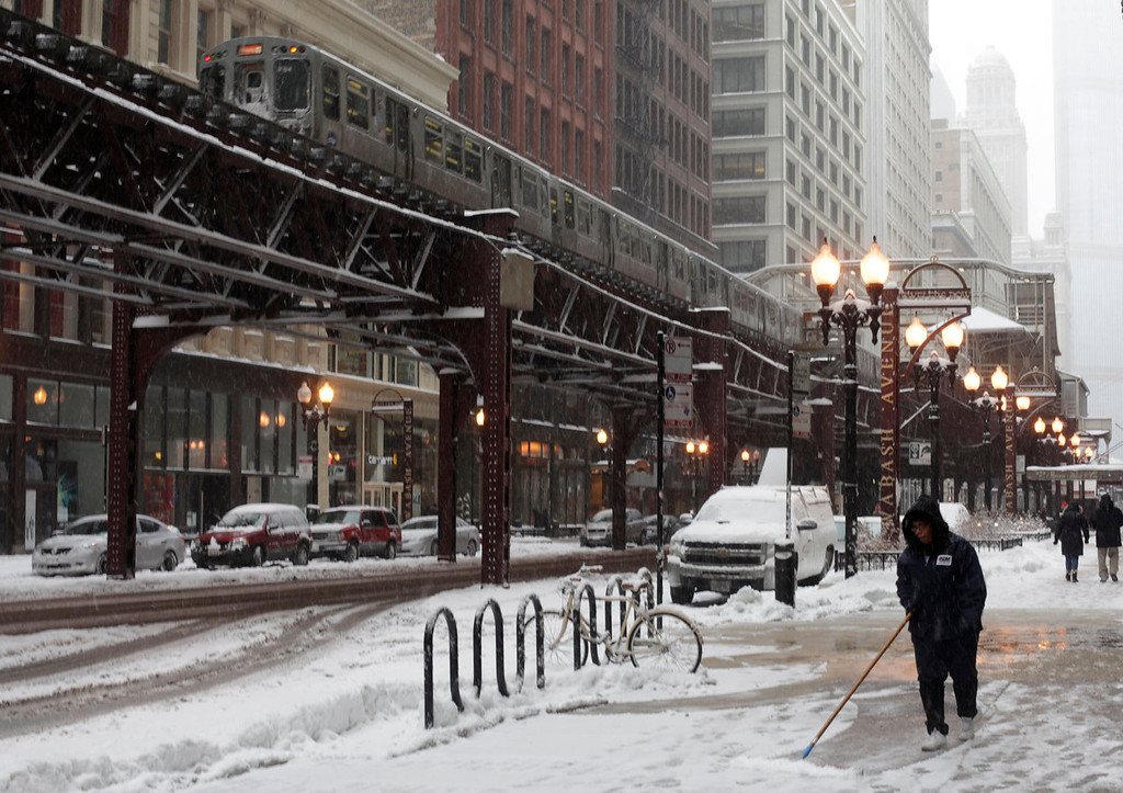 Description of . A downtown building maintenance crew clears the sidewalk as snow continues to accumulate on Thursday, Jan. 2, 2014, in Chicago. As much as a foot of snow or more was forecast for some areas in the Northeast overnight Thursday into Friday, and temperatures were expected to plummet, with some areas seeing highs just above zero, according to the National Weather Service. (AP Photo/Kiichiro Sato)