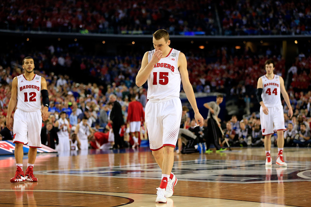 Description of . ARLINGTON, TX - APRIL 05: Sam Dekker #15 of the Wisconsin Badgers walks off the court after losing to the Kentucky Wildcats 74-73 in the NCAA Men's Final Four Semifinal at AT&T Stadium on April 5, 2014 in Arlington, Texas.  (Photo by Jamie Squire/Getty Images)