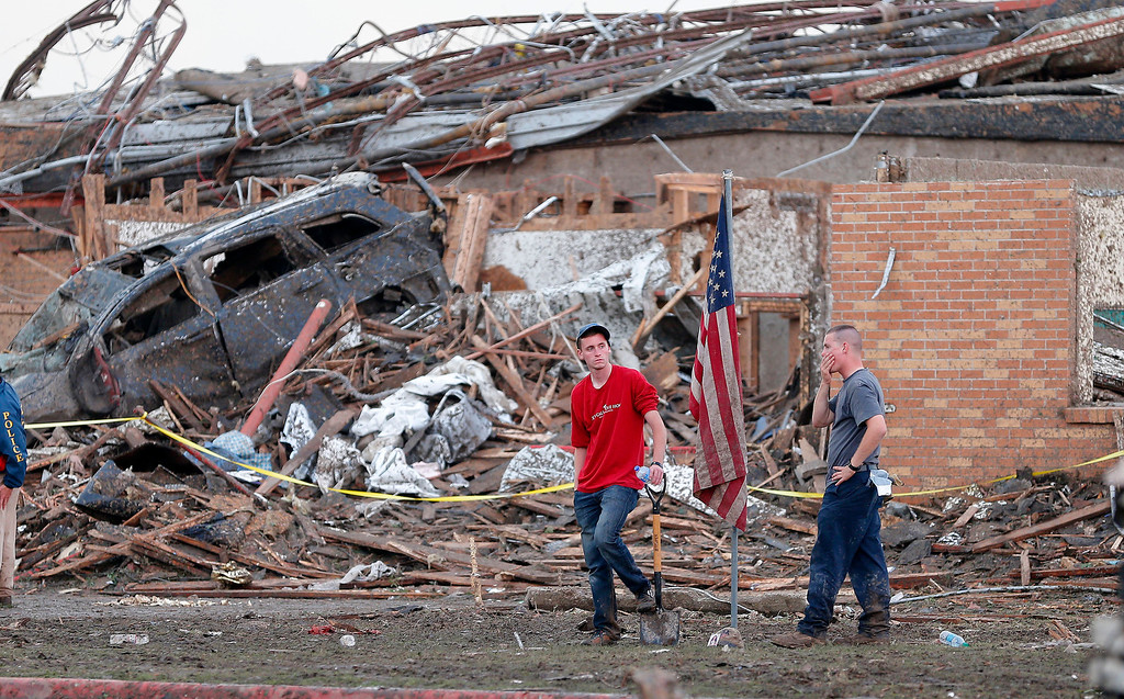 . Two men stand in front of Plaza Towers Elementary School in Moore, Okla., after a tornado destroyed a the school on Monday, May 20, 2013. (AP Photo/ The Oklahoman, Bryan Terry)