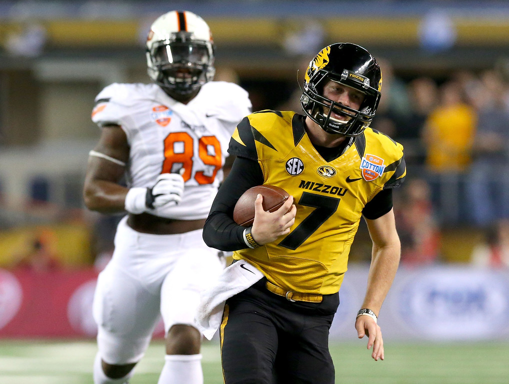 Description of . ARLINGTON, TX - JANUARY 03:  Quarterback Maty Mauk #7 of the Missouri Tigers runs the ball against the Oklahoma State Cowboys in the second quarter during the AT&T Cotton Bowl on January 3, 2014 in Arlington, Texas.  (Photo by Ronald Martinez/Getty Images)