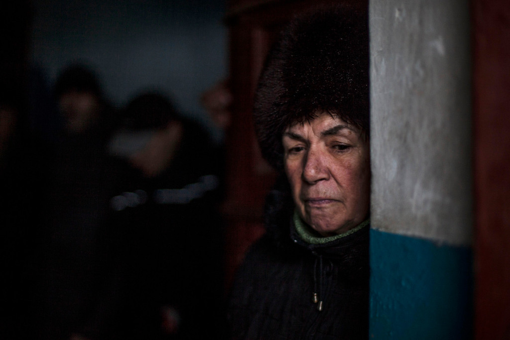Description of . A Ukrainian woman waits for shelling to abate as she shelters inside a building after a Ukrainian army shell hit a bus stop in the Kievsky district in Donetsk, Ukraine, Tuesday, Jan. 20, 2015. At least three civilians were killed in shelling Tuesday in eastern Ukraine as fighting continued between government and rebel forces in the separatist-held city of Donetsk. (AP Photo/Manu Brabo)