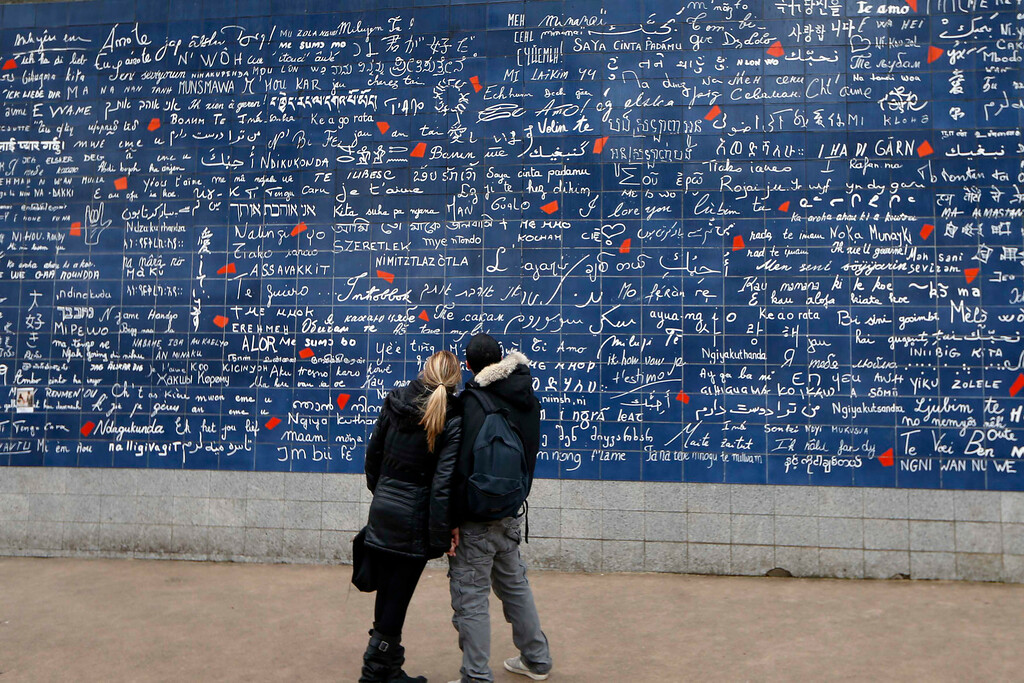 Description of . A couple stand in front the 'I love You : The Wall' art work by Frederic Baron and Claire Kito on Saint Valentine's Day in Paris February 14, 2013.   REUTERS/Charles Platiau