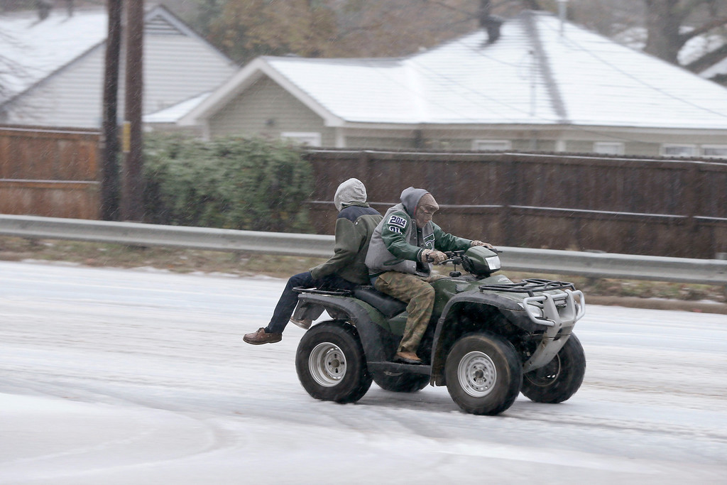 Description of . Two people ride a all terrain vehicle on a sleet-covered street in Little Rock, Ark., Friday, Dec. 6, 2013. Weather forecasters lifted an ice storm warning Friday for much of central Arkansas. (AP Photo/Danny Johnston)