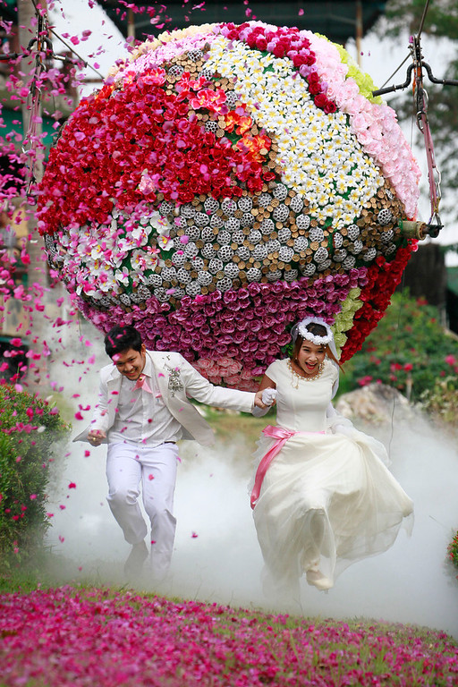 Description of . Prasit Rangsitwong, left, and Varutton Rangsitwong run away from a giant flower ball as a part of an adventure-themed wedding ceremony in Prachinburi province, Thailand, Wednesday, Feb. 13, 2013, on the eve of Valentine's Day. (AP Photo/Wason Wanichakorn)