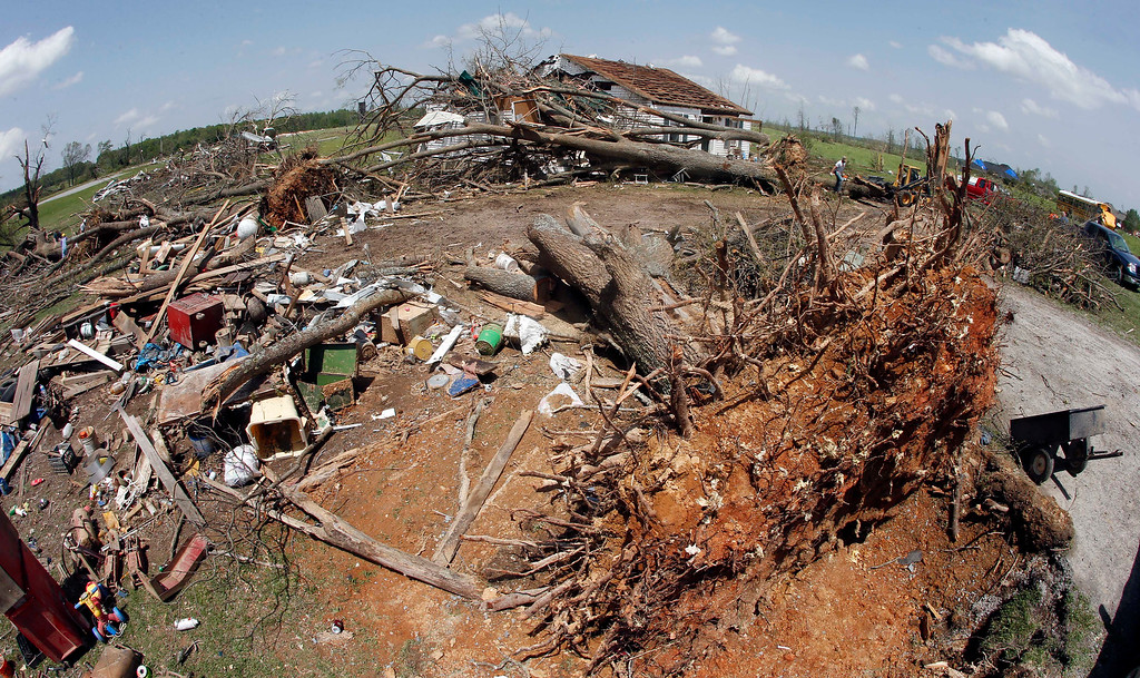 Description of . In this photo made with a fisheye lens, uprooted trees and debris fill the yard in front of a destroyed home on Tuesday, April 29, 2014, after storms came through Monday in Fayetteville, Tenn.  On Sunday evening, roughly 15 tornadoes carved a path of destruction in the South and the country's midsection, according to estimates from the National Oceanic and Atmospheric Administration's Storm Prediction Center. On Monday, around 50 tornadoes ravaged the South, the agency said. (AP Photo/Mark Humphrey)