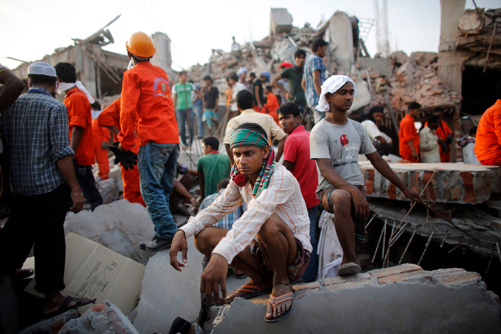 Description of . A rescue worker takes a break as he tries to rescue garment workers trapped in the Rana Plaza building which collapsed, in Savar, 30 km (19 miles) outside Dhaka April 24, 2013.  REUTERS/Andrew Biraj