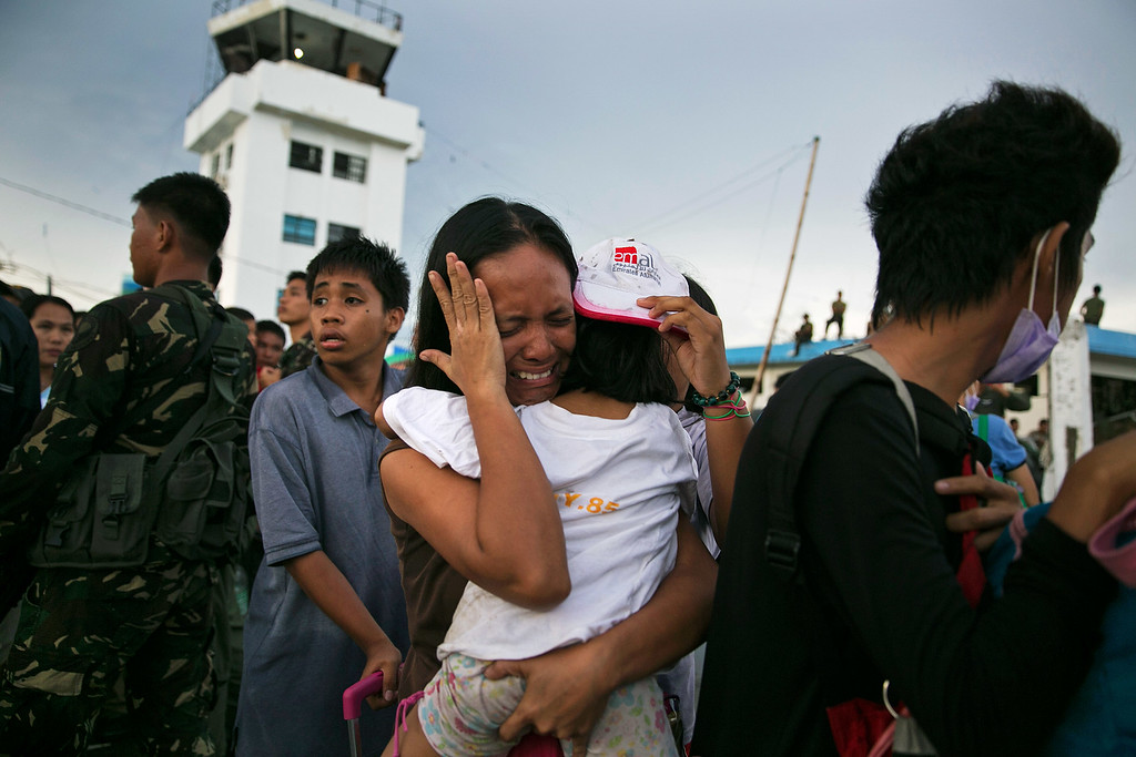 Description of . A woman carrying a child cries as other survivors of Typhoon Haiyan wait to board a C130 aircraft during the evacuation of hundreds of survivors of Typhoon Haiyan on November 12, 2013 in Tacloban, Philippines.  (Photo by Paula Bronstein/Getty Images)