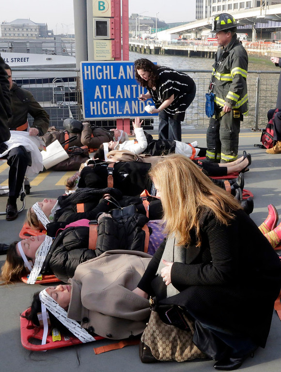 Description of . Injured passengers from the Seastreak Wall Street ferry wait to be taken to ambulances, in New York,  Wednesday, Jan. 9, 2013. The ferry from Atlantic Highlands, N.J., banged into the mooring as it arrived at South Street in lower Manhattan during morning rush hour, injuring as many as 50 people, at least one critically, officials said.(AP Photo/Richard Drew)