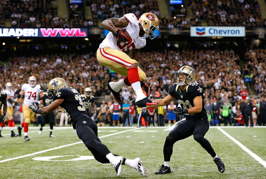 Description of . Vernon Davis #85 of the San Francisco 49ers leaps over Jabari Greer #33 and Chris Carr #31 of the New Orleans Saints at Mercedes-Benz Superdome on November 17, 2013 in New Orleans, Louisiana.  (Photo by Kevin C. Cox/Getty Images)