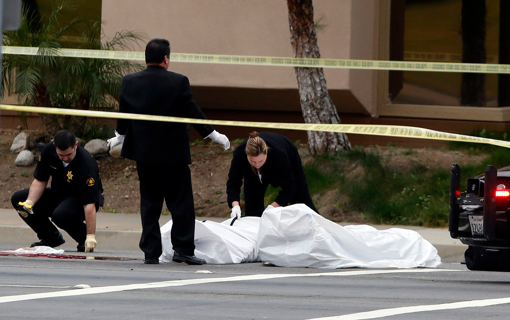 Description of . Orange County coroner's officials remove a body from the scene in Orange, Calif., Tuesday, Feb. 19, 2013.County. (AP Photo/Jae C. Hong)