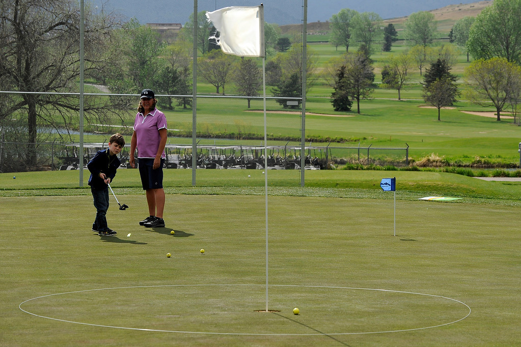 Description of . DENVER, CO - MAY 7: Nina Krats, right, helps Cameron Fay, 6, with putting practice during class at Foothills Golf Course on May 7, 2014, in Denver, Colorado. Foothills Park and Recreation is aiming to increase participation in its golf programs, especially in regards to youth involvement. (Photo by Anya Semenoff/The Denver Post)
