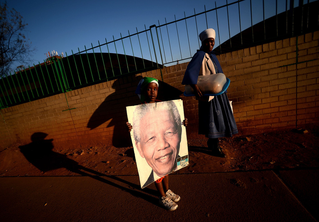 Description of . A woman and a little girl hold a Nelson Mandela picture in front of the Medi Clinic Heart hospital in Pretoria on July 3, 2013. Emotional crowds gathered outside the hospital where Nelson Mandela lay in critical condition, as relatives and clan elders made preparations for the revered former South African leader's final journey. Singing supporters amassed outside the Pretoria hospital where the 94-year-old anti-apartheid hero was fighting for his life.  FILIPPO MONTEFORTE/AFP/Getty Images