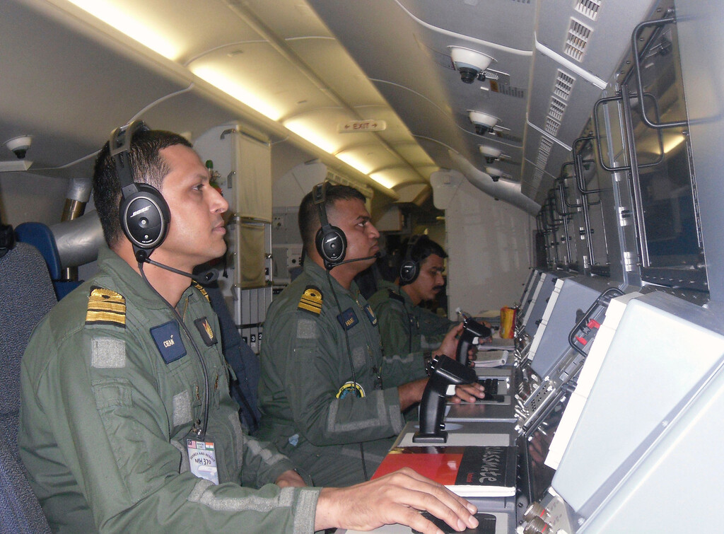Description of . This Sunday, March 23, 2014 photo released by the Indian Navy, shows the navy personnel on board a P-8I aircraft during a search operation for the missing Malaysia Airlines flight MH370 aircraft in the southern Indian Ocean. Ships rushed to the location of floating objects spotted Monday by Australian and Chinese planes in the southern Indian Ocean close to where multiple satellites have detected possible remains of the lost Malaysian airliner. (AP Photo/Indian Navy)