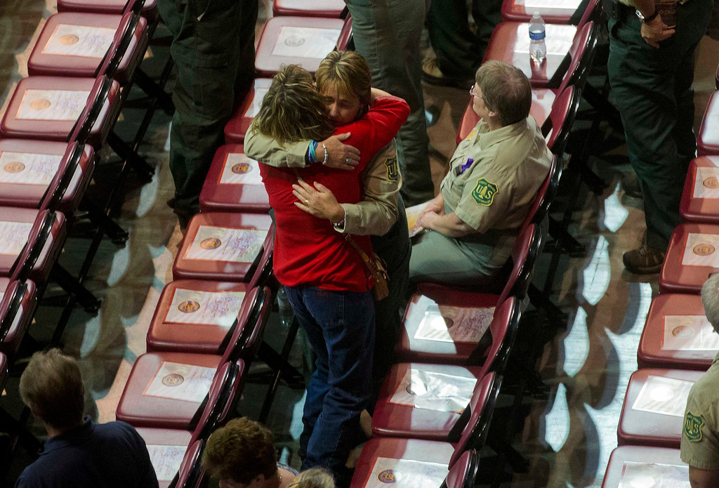 Description of . A Prescott National Forrest worker gets a hug from an unidentified woman before a memorial service for Yarnell firefighters at Tim's Toyota Center in Prescott Valley, Arizona July 9, 2013. REUTERS/Michael Chow/Pool