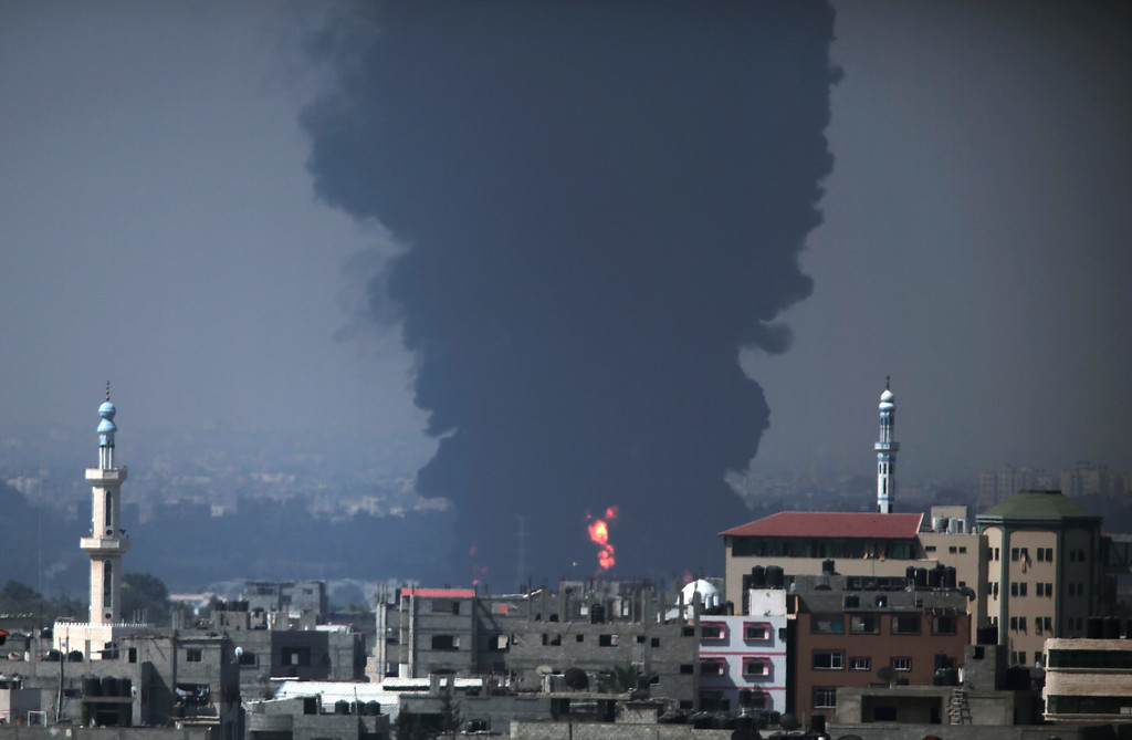 Description of . Seen from Gaza City, smoke and flames rise from Gaza's electricity distribution company plant after it was hit by Israeli strikes in the Nusseirat refugee camp, central Gaza Strip,Tuesday, July 29, 2014.  (AP Photo/Lefteris Pitarakis)