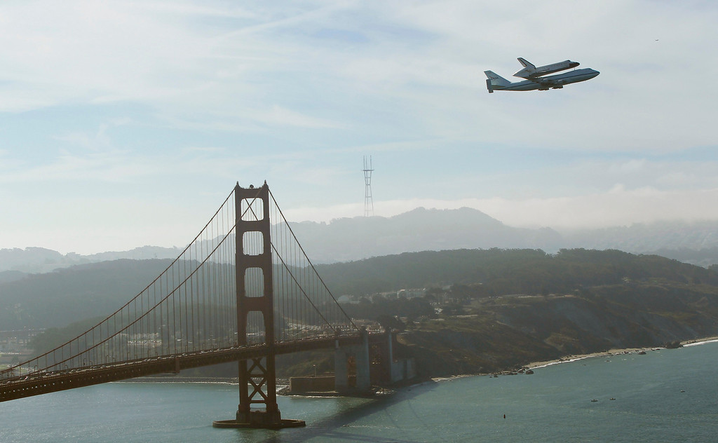 Description of . Retired space shuttle Endeavor is carried on the back of a NASA jet as it approaches the Golden Gate Bridge in San Francisco, California September 21, 2012. Endeavor will be moved to its permanent home at the California Science Center mid-October.  REUTERS/Robert Galbraith
