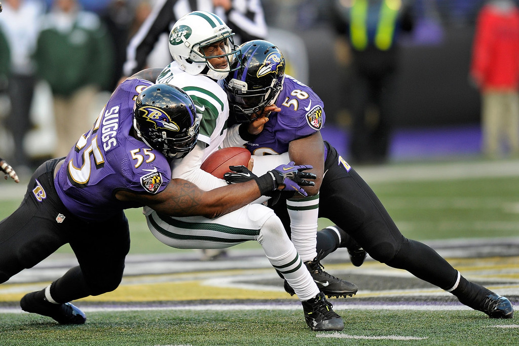 Description of . New York Jets quarterback Geno Smith, center, is tackled by Baltimore Ravens outside linebacker Terrell Suggs, left, and outside linebacker Elvis Dumervil, right, during the second half of an NFL football game in Baltimore, Sunday, Nov. 24, 2013. The Ravens won 19-3. (AP Photo/Nick Wass)