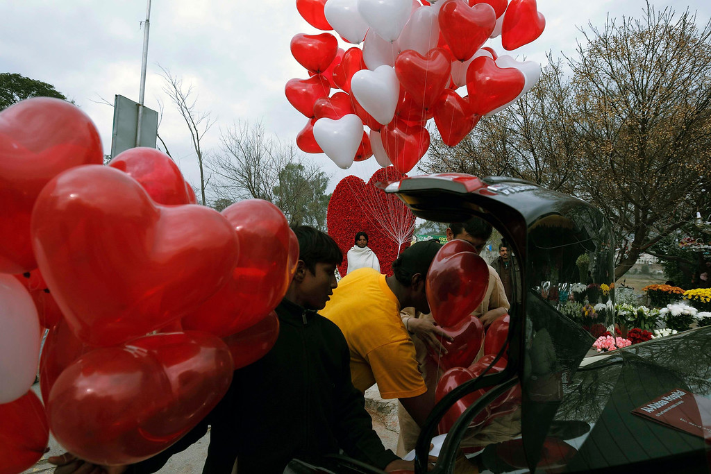 Description of . Men try to fit heart-shaped balloons in the trunk of a car on Valentine's Day in Islamabad February 14, 2013. REUTERS/Zohra Bensemra