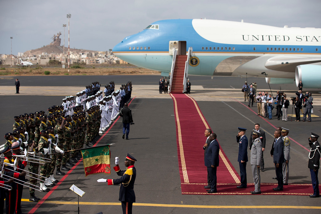 Description of . U.S. President Barack Obama, center left, and Senegalese President Macky Sall, center right, stand at attention while a Senegalese military band plays the American national anthem, as Obama prepares to board Air Force One to depart for South Africa, in Dakar, Senegal, Friday, June 28, 2013. President Obama is receiving the embrace you might expect for a long-lost son on his return to his father's home continent, even as he has yet to leave a lasting policy legacy for Africa on the scale of his two predecessors. (AP Photo/Rebecca Blackwell)