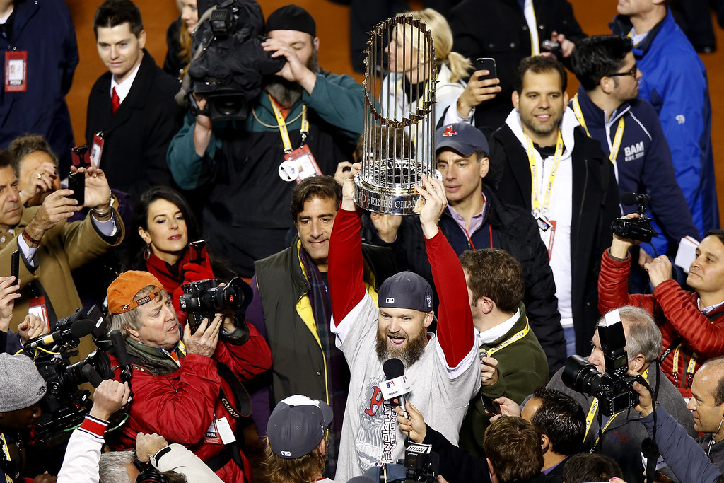 Description of . David Ross #3 of the Boston Red Sox holds up the World Series trophy after defeating the St. Louis Cardinals 6-1 in Game Six of the 2013 World Series at Fenway Park on October 30, 2013 in Boston, Massachusetts.  (Photo by Jared Wickerham/Getty Images)