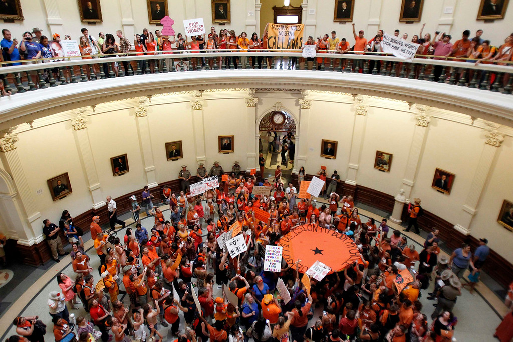 Description of . Abortion rights (in orange) and anti-abortion advocates (in blue) rally in the rotunda of the State Capitol, as the state Senate meets to consider legislation restricting abortion rights in Austin, Texas July 12, 2013. The Republican proposal that would ban most abortions in Texas after 20 weeks of pregnancy moved toward a possible final vote in the state Senate Friday, and Democrats fiercely opposed to the measure conceded they will not be able to stop it.   REUTERS/Mike Stone